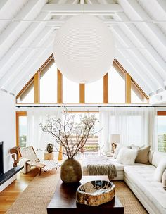 Bright living space with wooden beams, a large paper lantern, and a white sectional
