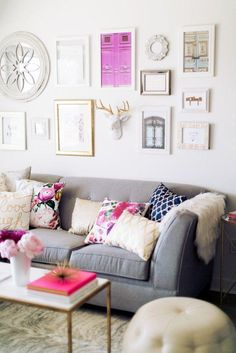 White, gray and dark pink feminine and sophisticated living room -- love the gallery wall above the sofa, and plethora of comfy and colorful throw pillows!