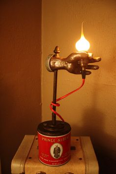 Unique handheld flame tip bulb lamp atop vintage Prince Albert tobacco can. on Etsy, $80.00