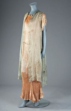 Mariano Fortuny ensemble, circa 1920-1930. 1920-30 Apricot silk Peplos gown and a stencilled tabard, edged with striped white Murano beads to the shoulders.