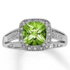 A cushion-cut peridot provides captivating color in this fine jewelry ring for her. Brilliant diamonds encircle the center and adorn the band of this 10K white gold ring, which is finished with milgrain edging. Diamond Total Carat Weight may range from .085 - .11 carats.  Gently clean by rinsing in warm water and drying with a soft cloth.