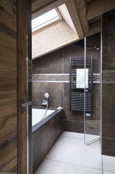 Salle de bains haut de gamme sous les toits, avec baignoire, seiche serviettes noir, carrelage marron, vasistas...
