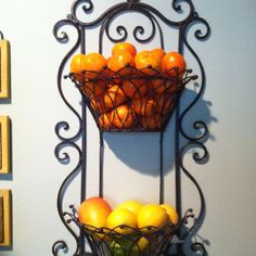 Wrought iron wall planter used to hold fruits and vegetables.