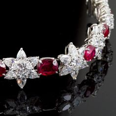 A very fine diamond and ruby in platinum bracelet. Comprised of nine diamond florets formed from 54 pear shaped and 9 round brilliant center diamonds. Linked by 9 deep red oval shaped rubies. Diamonds