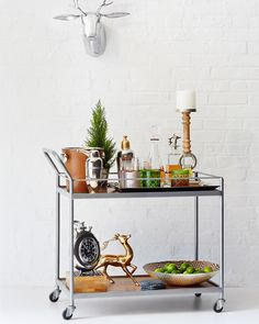 "To give your bar cart a ""warmer"" look, add some foliage, like a potted plant, and wood and brass accents.   - ELLEDecor.com"