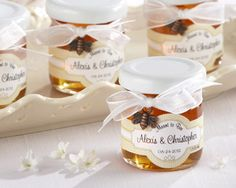Sweet clover honey in adorable jars makes a special wedding favor when decorated with personalized label. White ribbon and bronze bee charm.