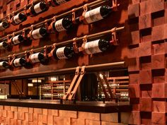 Custom wine bar installation using leather bicycle wine racks and custom brass knobs.