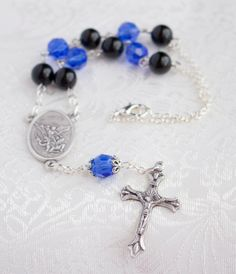 This beautiful one decade car rosary features five 8mm sapphire blue crystal beads and six 8mm black Agate stone beads. The Our Father bead