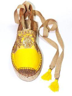Sandalias alpargatas con suela de plataforma, hechas de loneta amarilla de algodón orgánico, con bordado de pasamanería en hilo dorado y lentejuelas sobre tul transparente. Talonera color marrón y cintas color arena para enlazar en la pierna. Borlas amarillas en los extremos de