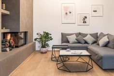 Greek apartment by Normless Architecture Studio and Workspace borrows trends from Scandinavian design in its low-key modernism. Smooth stone wall on left with fireplace.