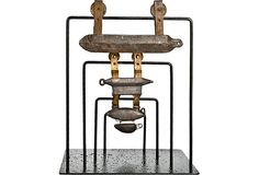 """Set of four vintage trolling line pulley weights mounted on a graduated, reclaimed iron stand. Two Ajon weights, a trolling weight, and a Godwin fish-shaped weight. Large Ajon, 6.5""""L x 3""""H x .5""""W; medium Ajon, 3.5""""L x 3""""H x .25""""W; trolling, 2.75""""L x 2.25""""H x .25""""W; fish-shaped, 2.75""""L x 2.25""""H x .25""""W. The Ajons have embossed logos, the rest, no maker's marks."""