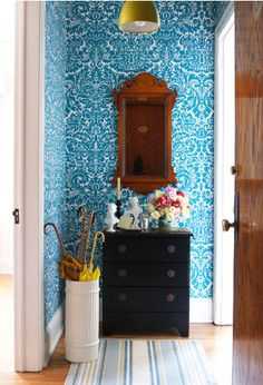 Contrasting colors and pattern make it stand out! Love the wallpaper pattern and the rich color of the wood.