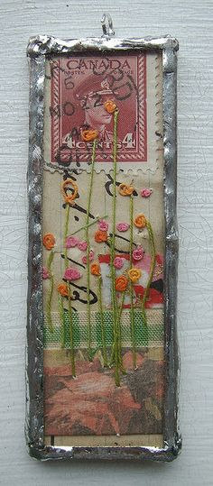 collage with stamp, embroidery, fabric under soldered glass