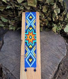 Weefgetouw Beaded Manchet armband met Native American Star phantasy patronen ontworpen door mij. Ik gebruikte hier de bead loom techniek met native Amerika stijl patronen in flitsende kleuren oranje en blauw gekleurde glazen kralen. Gemaakt uit Tsjechische Rocailles en 2 grote kralen als een gesp.  Deze armband meet 18.3 cm of 7,2 inch en is 3,6 cm of 1.42 inch breed.  Kleur en grootte kunnen worden gewijzigd om te bestellen! Bij het bestellen, gelieve te schrijven me een kort bericht over…