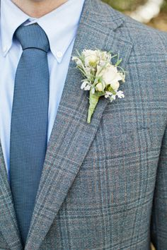 A sweet white boutonniere pinned to a tweed suit. Photo by Caroline Joy