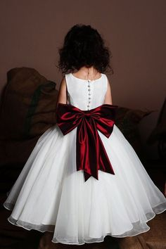 White flower girl dress with a red bow - http://themerrybride.org/2015/10/11/flower-girl-dresses-3/