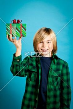 smiling boy showing his christmas gift. - Smiling boy showing his christmas gift while standing against turquoise background, Model: Josh Chapman