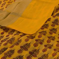 """This """"Yellow"""" #handblock printed Banarasi Organza Silk Sari from Parisera is woven with floral motifs all over the body that is set off by a gold zari border and pallu. The yellow blouse completes the sari."""