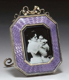 A SILVER-GILT GUILLOCHÉ ENAMEL MINIATURE FRAME marked Fabergé and with the workmaster's mark of Johan Victor Aarne, St. Petersburg, 1896-1908, with scratched inventory number 3083 Of rectangular form with cut corners, the pyramidal sloping frame of translucent mauve guilloché enamel enclosing a photograph of Empress Alexandra Feodorovna holding her daughter Grand Duchess Tatiana, within a gold dot and dash border, surmounted by a ribbon crest, with scroll strut, marked on rim and strut