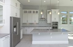 Contemporary kitchen with white cabinets with glass doors and gray quartz countertops Gray Quartz Countertops, White Cabinets White Countertops, White Shaker Kitchen Cabinets, Custom Kitchen Cabinets, Kitchen Cabinet Design, Kitchen Island, Modern Cabinets, Grey Kitchen Floor, Modern Kitchen Backsplash