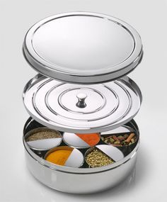"The Spice Tiffin - Patent Pending: stainless steel tin has 7 removable bowls with a half-moon ""catch"" to level your measures right in the container...comes with a standard tablespoon and teaspoon...to keep spices fresh it has a thin lid that nestles into the main box and a main lid that covers the entire container...$49.95"