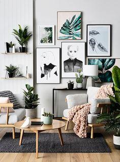 Modern Scandinavian living room with wall art and green plants.