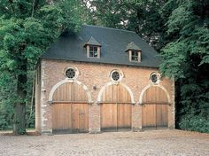 Garage made with three arches - wheel windows and arches in white stone. Rik Storms Ancient Building Materials