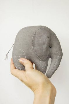 Meet Ella, a small grey baby elephant - look at this darling small softie! Isnt she the cutest baby girl elephant that can fit in you palm (well almost :) )? This baby girl elephant plush is made of grey linen (the shade of grey may look different on your display - it highly depends on the settings of your own device). I kept her simple - she has a few swirl stitches on her legs and a bit of grey-to-purple stitchery on her head and trunk. The back of her ears is lined with pink fabric with…