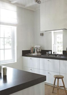 uncluttered white cabinets, black soapstone countertops, stainless appliances and fittings