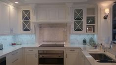 """White painted custom built kitchen, shaker style doors, with custom designed mantle hood. Best hood insert used pk29. X Mullin doors with clear glass inserts. Wolf 36"""" cooktop and 36"""" Wolf oven. Quarts counterparts and back splash with LED light strip. Plug mold strip also under cabinets. Hardware by Atlas Hardware company. CUSTOM DESIGN BY: Jon Divincenzo CUSTOM BUILD BY: Final Touch Moulding and Cabinetry."""