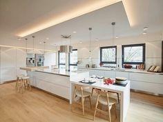 meubles blanc et bois clair et plancher assorti dans la cuisine avec ilot et table à comptoir lunch