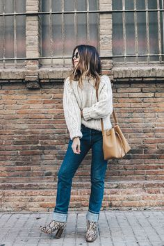 Sara of Collage Vintage is cozy in a cable knit sweater, cuffed jeans, snake print boots, and a bucket bag Ever wonder which NYC outfits the city's coolest girls wear over and over again? We rounded them up. Booties Outfit, Outfit Jeans, Fall Winter Outfits, Autumn Winter Fashion, Fashion Fall, Snake Print Boots, Snake Boots, City Outfits, New York Outfits
