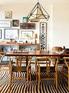 Eclectic dining room space with a gallery wall, a geometric pendant light, and wishbone chairs
