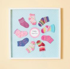Can't bear to throw out those adorable baby socks? Frame 'em! Here's how: Cut foam core to fit a shadow box, fold fabric or paper around the foam core, and secure with tape. Arrange the socks and attach with glue dots. Write the name and birth date on card stock and attach. Put the foam core in the shadow box, hang your sock flower on the wall, and admire!