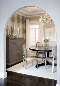 Amoroso Design Lovely, elegant gray dining room design with gray walls paint color, arched doorway, tall gray painted buffet chest, mercury glass vases accents, Romo gray