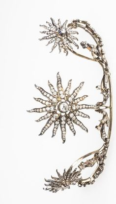 A VICTORIAN DIAMOND TIARA formed from three graduated open-work sunbursts, each set with a diamond to the centre, pave-set overall with graduated round old-cut diamonds, within a millegrain-set diamond leaf and scrollwork frame, set in silver and gold, the tiara detaches from the frame to form three separate pendants or brooches and a necklace, with four loose yellow gold screw fitments.