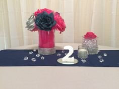 Navy blue, hot pink and silver wedding table centerpieces Handmade paper Roses in a 7x4 inch glass vase filled with hot pink tulle, a 4x4 inch glass vase filled with clear acrylic scatter and a votive candle. Each with sparkling silver rhinestone ribbon mesh around the bottom.