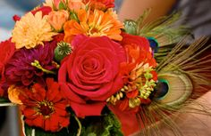 Red and Orange Floral Bouquet... I love the addition of the plum dahila and the daises with the reddish center. No peacock feathers though