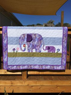 Handmade baby quilt perfect for a shower gift! Excellent size for crib, floor or wall-display. Appliqued Mother & Baby elephant pattern with modern, graphic fabrics and design. Colors are also great for a growing up toddler! This handmade quilt features premium quilters cotton in purples, blues and greens. The modern Elephant Family pattern is enhanced by custom, modern machine quilting, with an ear that flaps. The backing is a periwinkle bunny pattern on white. This unique quilt was cre...
