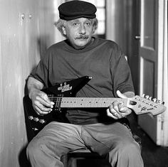 Einstein playing electric guitar.        This is the coolest picture ever.    he is such an awesome guy whats not to like