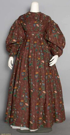 *  PRINTED COTTON DAY DRESS, c. 1825 Brown twill w/ block printed apricot, blue & green block florals, raised inserted waistband, high neck, large gigot sleeve