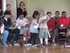 Grade 1 students give a Grade 8 student a rose at the Rose Ceremony for the upcoming 8th grade commencement. 2014-15