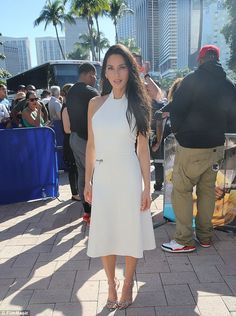 White hot! The brunette beauty sizzled in a skintight white frock that featured her slim physique and feminine curves