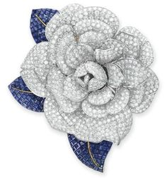 Elizabeth Taylor, DIAMOND AND SAPPHIRE FLOWER BROOCH Designed as a pave-set Diamond Camellia Blossom, extending three square-cut Sapphire leaves, mounted in White and Yellow Gold.