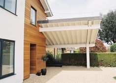 Remodelling project on 1960s estate house in Hampshire by www.spaceandstyle.co.uk. The project introduced a cantilevered carport with only one structural column for support. The structure of the roof and cantilevered beams were left exposed for effect.