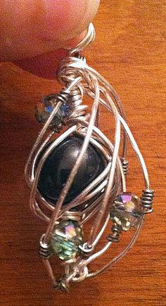 Silver wire wrapped pendant with a 10mm black glass pearl and 4 rainbow faceted crystals. The piece is 1- 3/4 long and 1 at its widest point. The