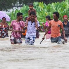 Sri Lankan people wade through floodwaters after heavy rain in Colombo