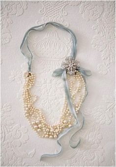 "Would be perfect for some of my grandmother's old jewelry - ""For this vintage style necklace, fold a long pearl necklace or two in half, loop ribbon through  each side, tie bow on the side then pin a broach by the bow for some extra glamor."""