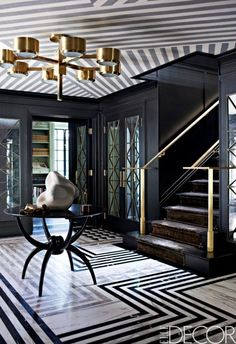 A black white and gold entry with striped floor and ceiling makes a stunning entrance! Black and White bold design