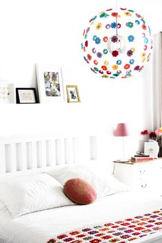 A bedroom featuring a memorable light pendant with colorful crocheted flowers on it.